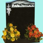 Black headstone with carved country scene